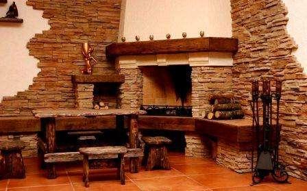 Стены из камня прекрасно сочетаются с камином, винтажной мебелью, выполненной под старину