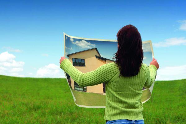 женщина с фотографией дома в руках